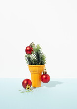 Artificial Spruce Branches Decorated With Red Christmas Baubles Placed In Ice Cream Cup On Table In Studio On Blue Background