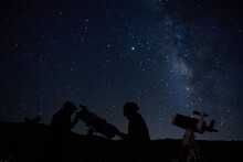 Silhouettes Of Anonymous Scientists Using Telescopes While Exploring Night Starry Sky With Milky Way In Darkness