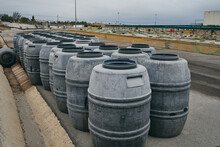 Rows Of Shabby Metal Barrels Placed In Shabby Industrial Place Of Factory On Cloudy Day