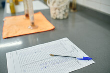 High Angle Of Scientific Report Of Experiment Placed On Table With Pen In Contemporary Chemical Laboratory