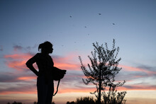 Low Angle Side View Of Silhouette Of Anonymous Female Farmer Standing In Garden In Rural Area And Enjoying Sundown After Working Day