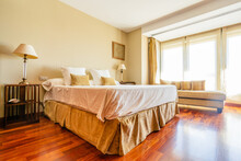 Cozy Spacious Bed With Cushions And Coverlets In Room With Wooden Parquet And Panoramic Windows