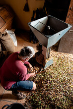 From Above Farmer Going Down On One Knee And Holding Handful Of Nuts Over Bucket With Almonds And Heap Of Shells On Floor