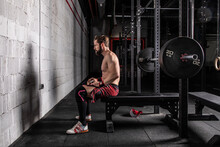 Side View Of Determined Sportsman With Strong Naked Body Sitting On Bench Press With Barbell And Getting Ready For Workout