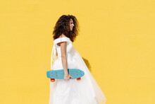 Side View Of Bride In White Dress Standing While Holding Longboard Against Yellow Background In Sunlight