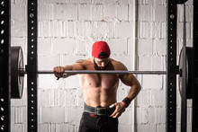 Strong Male Athlete With Naked Torso And In Weightlifting Belt Standing Near Barbell During Workout In Gym