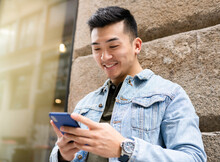 Content Young Asian Male In Casual Outfit Browsing On Mobile Phone While Standing Near Stone Wall Of Urban Building