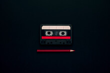 Top View Of Vintage Compact Audio Tape With Paper Sticker Placed And Red Pencil On Black Background