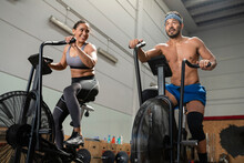 From Below Of Cheerful Sportswoman And Sportsman Cycling On Stationary Air Bikes During Active Training In Modern Gym