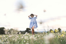 From Below Full Body Delighted Female In Short Blue Dress Walking Through Meadow Covered With Grass And Flowers Next To Forest And Mountain Valley Under Cloudless Sky In Daytime