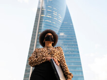 Low Angle Of Confident African American Female In Protective Mask Holding Netbook While Standing Against High Skyscraper