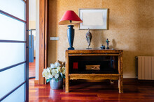 Apartment Hallway With Shiny Wooden Parquet And Flowers Near Table With Antique Statues
