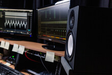 Contemporary Stereo Speaker Placed On Table With Monitors In Dark Music Recording Studio