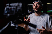Confident Male Singer Sitting In Music Recording Studio And Shooting Video On Professional Camera For Blog