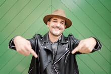 Trendy Friendly Male In Hat And Leather Jacket Smiling And Looking At Camera On Green Gate Background