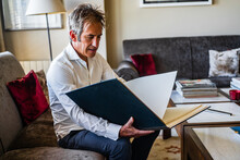 Aged Cheerful Happy Male Reviewing Business Plan While Resting On Soft Comfortable Sofa Near Table With Papers