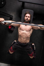 From Above Of Strong Focused Male Athlete Lying On Bench Press And Doing Exercises With Heavy Barbell During Workout In Gym