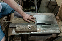 High Angle Of Male Carpenter Sitting At Workbench And Cutting Piece Of Wooden Plank With Sharp Circular Saw While Working In Shabby Workshop