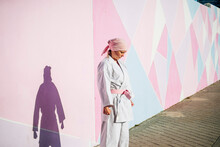 Side View Of Determined Thoughtful Mature Woman In Pink Head Cover And Belt Fighting Karate In Cancer Battle Concept In The Street On Pink Wall With Eyes Closed