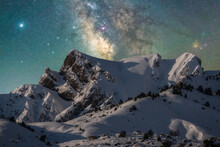 Spectacular View Of High Rough Ridge Covered With Snow Under Colorful Starry Sky During Milky Way Phenomenon
