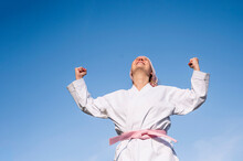 From Below Determined Cheerful Mature Woman In Pink Head Cover And Belt Fighting Karate In Cancer Battle Concept Standing On Blue Sky Background Looking Up