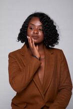 Gentle African American Female In Brown Jacket And With Curly Hair Touching Cheek And Calmly Looking Away On Gray Background In Studio