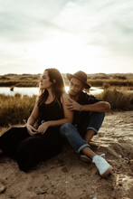 Young Loving Couple In Casual Clothing Sitting Together Looking Away On Coast Of Reservoir Surrounded By Dry Grass In Meadow In Sunlight