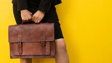 Crop Anonymous Female In Skirt With Stylish Brown Leather Handbag Standing Against Yellow Background