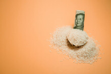 High Angle Of Pile Of Rice In Bowl With Chinese Renminbi Bill Arranged On Peach Background In Studio
