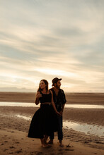 Full Body Of Young Barefoot Man And Woman In Casual Clothing Holding Hands And Looking In Opposite Directions While Standing On Wet Sand Covered With Footprints Under Evening Sky
