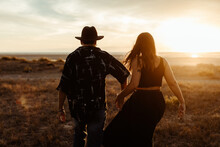 Back View Of Unrecognizable Young Couple In Casual Clothing Running Through Meadow Covered With Yellow Dry Grass At Dawn