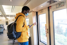 Side View Of African American Male Traveler In Mask And Earphones Standing In Train While Browsing Smartphone And Listening To Music
