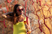 Smiling Young Female In Bright Yellow Sundress And Sunglasses Enjoying Tasty Colorful Ice Cream In Waffle Cone While Standing Amidst Leafless Red Tree Branches Against Shabby Stone Wall Of Old Building