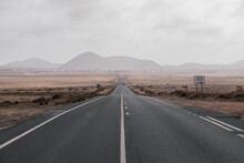 Endless Asphalt Road Going Through Dry Savanna In Mountainous Terrain On Overcast Day