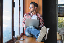 Young Trendy Remote Worker In Eyeglasses With Netbook Sitting With Crossed Legs On Windowsill Near Disposable Glass Of Coffee While Looking Out Window