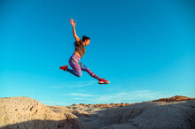 From Below Full Body Of Active Energetic Female In Sportswear Leaping High Above Sandy Slope Of Desert Terrain Against Blue Cloudless Sky