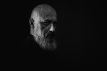 Close Up Photo, Portrait Of A Serious, Thoughtful, Bearded Man On A Dark Background Confident And Dramatic Looking Straight. Concept Of Male Portrait. Black And White Photo. Low Key