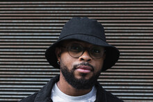 African American Bearded Guy With Missing Tooth In Eyeglasses Wearing Trendy Casual Outfit And Hat Looking At Camera While Standing Against Shuttered Wall