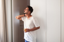 Side View Of Young Male In Casual Clothes Drinking Fresh Juice And Observing Street While Standing Near Window In Modern Apartment In Morning With Eyes Closed