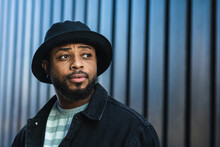 African American Bearded Guy With Missing Tooth Wearing Trendy Casual Outfit And Hat Looking Away While Standing Against Shuttered Wall