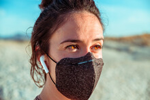 Side View Of Confident Young Sportswoman In Black Protective Mask Listening To Music With Wireless Earbuds While Recreating During Training In Rough Desert Badlands Looking Away