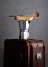 Simple Composition Of Coffee Maker With Wooden Old Spoon And Bread Stick Placed On Leather Suitcase