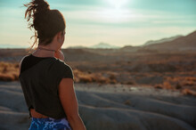 Back View Of Calm Unrecognizable Female In Sportive Outfit Contemplating Amazing Scenery Of Rough Stony Badlands At Sunset Time