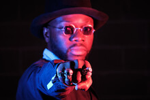 Serious African American Male In Stylish Black Clothes Showing Fist With Rings At Camera While Standing On Black Background In Studio With Neon Illumination