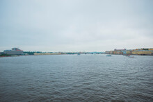 Neva River With Floating Boats And Historic Buildings On Embankment Under Gray Cloudy Sky In Overcast Day In Saint Petersburg