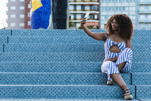 Full Body Positive African American Female In Striped Apparel Smiling And Taking Selfie While Sitting On Stairs On City Street