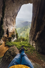 From Above Of Crop Anonymous Tourist With Crossed Legs Admiring Mossy Cave And Mountains Under Cloudy Sky In Fog