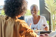 Cheerful African American Female With Short Hair Sitting At Table On Terrace Of Restaurant With Friend With Curly Hair Eating Sushi With Chopsticks While Laughing And Having Fun Together
