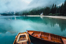 From Above Wooden Boat With Paddles Floating On Turquoise Water Of Calm Lake On Background Of Majestic Landscape Of Highlands