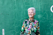 Elegant Elderly Female In Stylish Outfit Standing Against Green Wall On Parking Lot Looking Away